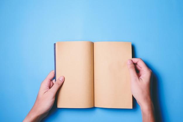 Odgórny widok ręki trzyma pustą książkę przygotowywającą