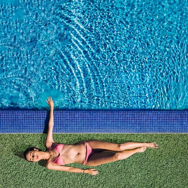 Odgórny widok relaksuje obok basenu dziewczyna