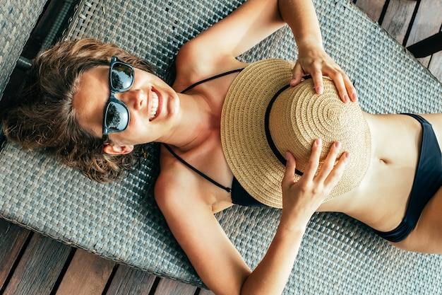 Odgórny widok relaksuje w pokładu krześle blisko basenu piękna młoda kobieta