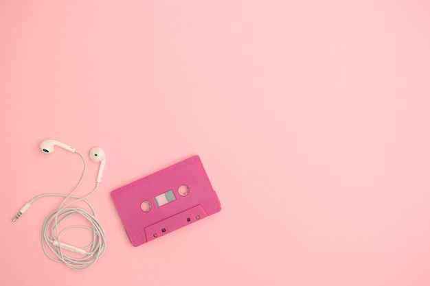Odgórny widok retro taśmy kaseta z słuchawką na różowym tle. koncepcja muzyki miłości