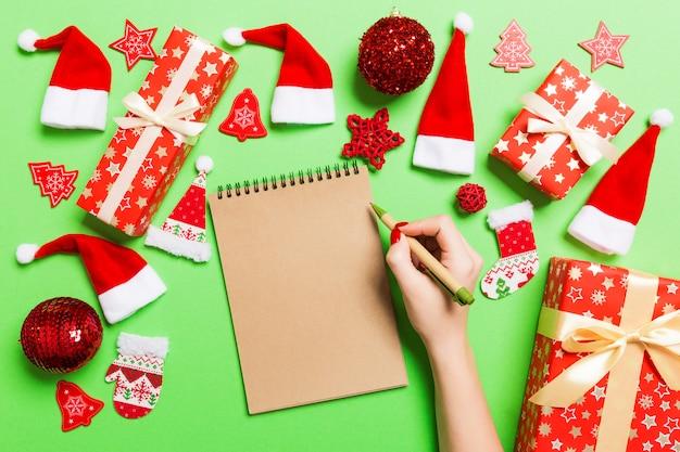 Odgórny widok robi niektóre notatkom w noteebok na zielonym tle żeńska ręka. dekoracje noworoczne i zabawki. pojęcie czasu bożego narodzenia