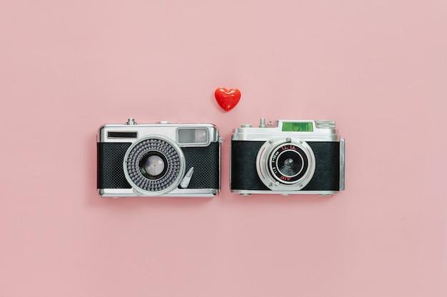 Odgórny widok rocznik stara kamera i mały czerwony serce na różowym pastelowym tle.