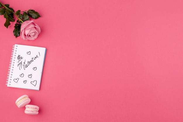 Odgórny widok róża i notatnik z macarons i kopii przestrzenią