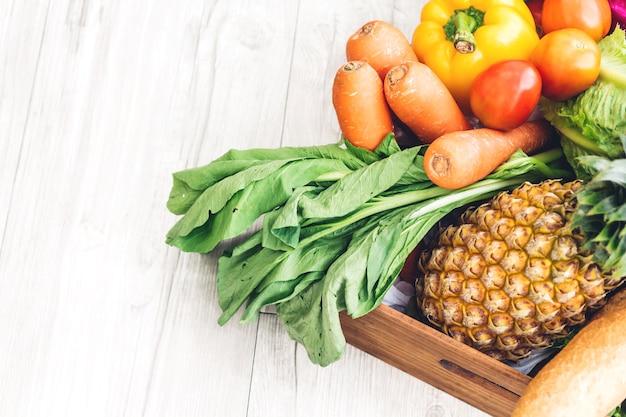 Odgórny widok różni świezi owoc i warzywo na białym drewnianym stole