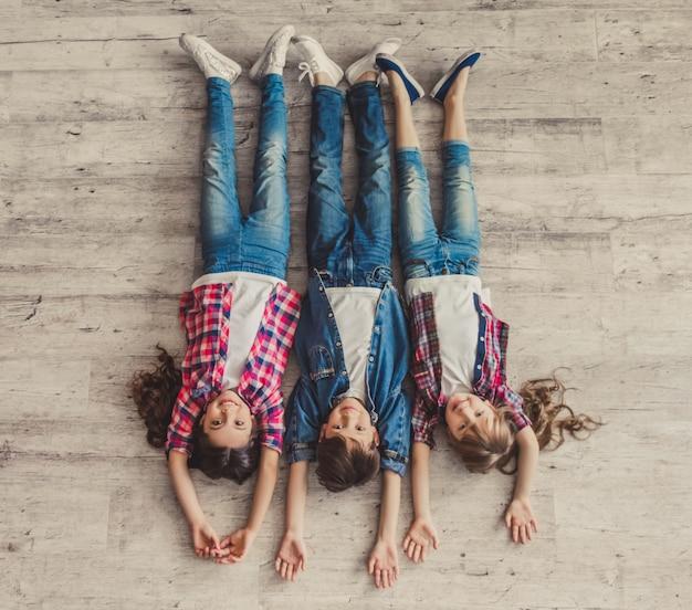 Odgórny widok rozochoceni dzieciaki patrzeje kamerę i ono uśmiecha się.