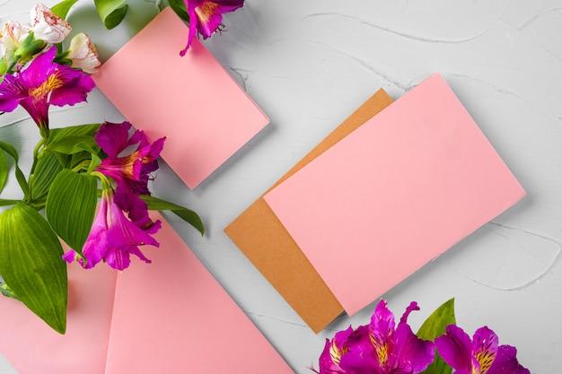 Odgórny widok różowy papierowy list i kwiaty z kopii przestrzenią