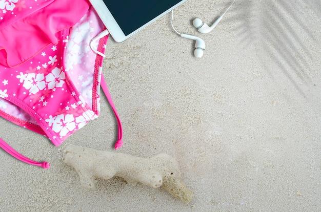 Odgórny widok różowy swimsuit i smartphone na piasek plaży.