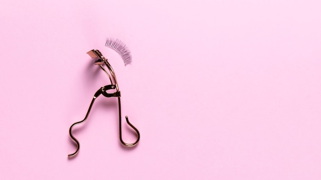 Odgórny widok rzęsy curler na różowym tle