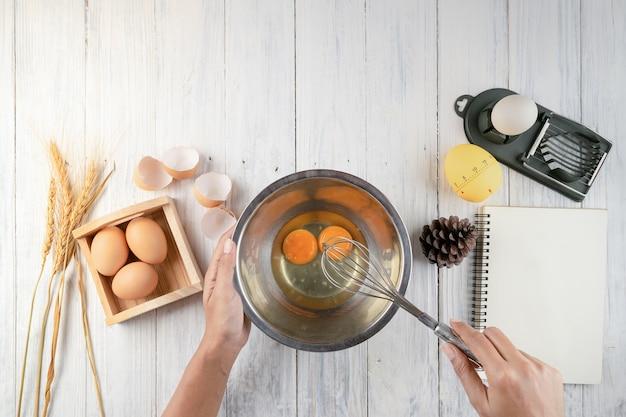 Odgórny widok składa łamanie jajko w puchar kobieta szef kuchni. żeński szef kuchni trzepie jajka w pucharze
