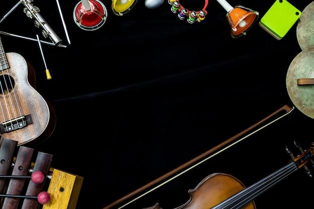 Odgórny widok skrzypcowa gitara i ukulele z instrumentami perkusyjnymi na czarnym tle