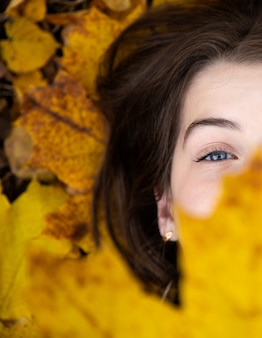 Odgórny widok śliczna dziewczyna z niebieskimi oczami który w spadku kłama na ziemi i trzyma pięknego żółtego liścia klonowego przed ona.