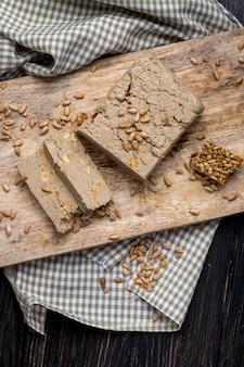 Odgórny widok smakowici plasterki chałwa z ziarnami słonecznika na drewnianej desce