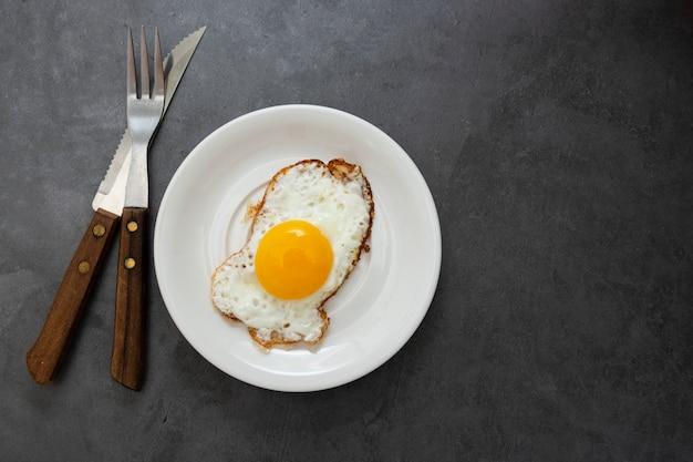 Odgórny widok smażącego jajka zakończenie up. jedzenie na śniadanie. jajko sadzone na miękko po słonecznej stronie. skopiuj miejsce