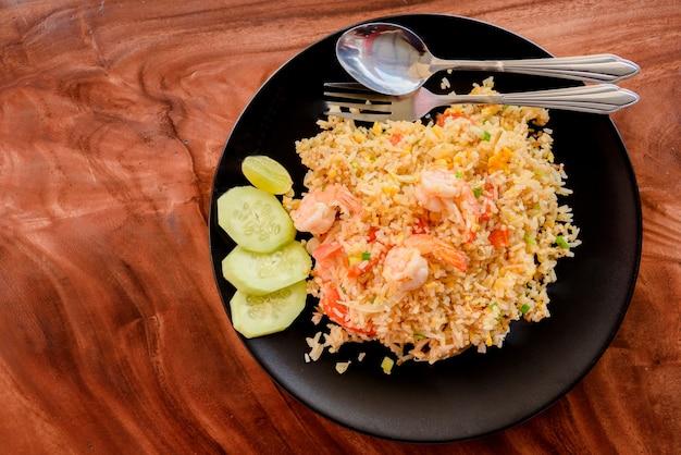 Odgórny widok smażący ryż z garnelą na naczyniu na drewnianym stole