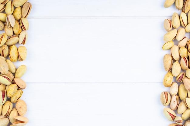Odgórny widok solone piec pistacje na białym tle z kopii przestrzenią