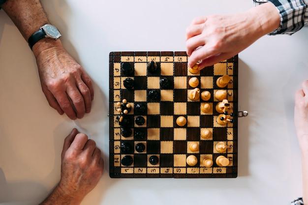 Odgórny widok starsze osoby dobiera się bawić się szachy w emerytura domu