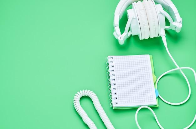 Odgórny widok stół nastoletnie dziecko, składów hełmofonów notatnik na jasnozielonym tle
