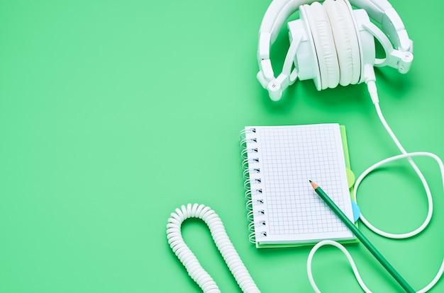 Odgórny widok stół nastoletnie dziecko, składów hełmofonów notatnika ołówek na jasnozielonym tle