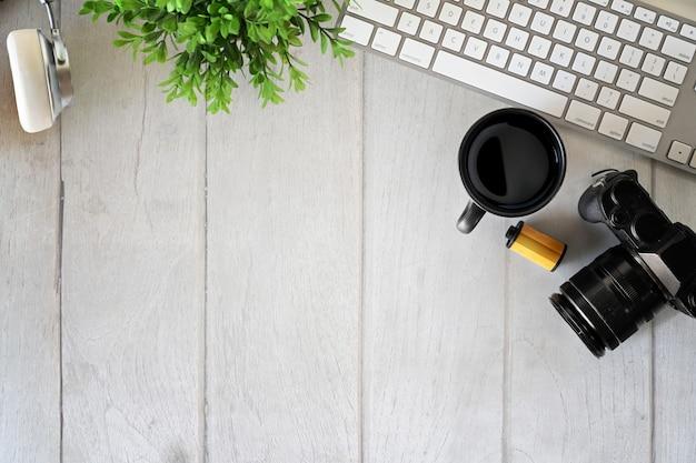 Odgórny widok strzelający biurko fotografa miejsce pracy z klawiaturową komputeru i kopii przestrzenią.