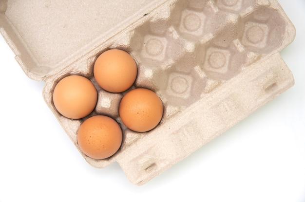 Odgórny widok surowi kurczaków jajka w jajecznym pudełku dalej na białym tle.