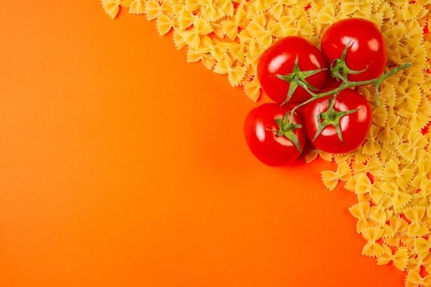 Odgórny widok surowy makaronu farfalle z wiązką pomidory i kopii przestrzeń na pomarańcze
