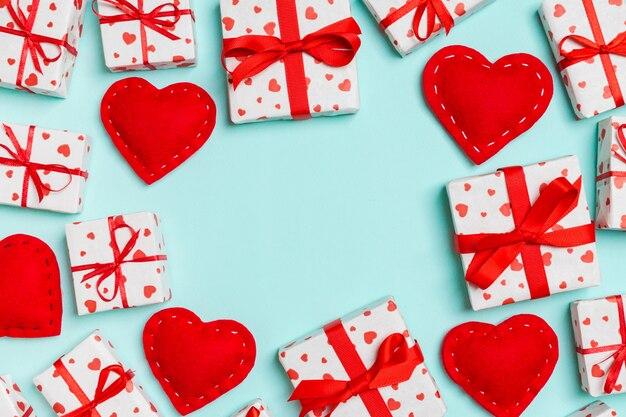 Odgórny widok świąteczni prezentów pudełka i czerwoni tekstylni serca na stole z kopii przestrzenią.