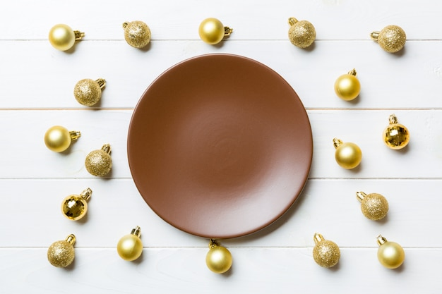 Odgórny widok świąteczny talerz z złotymi baubles na drewnianym tle. ozdoby choinkowe i zabawki. nadejście nowego roku