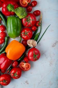 Odgórny widok świezi dojrzali warzywa pomidory zielonego chili pieprzu dzwonkowego pieprzu czosnku brokuły i cebula na marmurowym tle