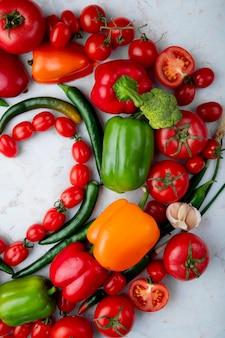 Odgórny widok świezi dojrzali warzywa układający w kierowym kształcie czereśniowych pomidorów zielonego chili pieprzu dzwonkowego pieprzu czosnek i cebula na marmurowym tle