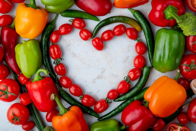 Odgórny widok świezi dojrzali warzywa układający w kierowym kształcie czereśniowych pomidorów zielonego chili pieprzu dzwonkowy pieprz na marmurowym tle