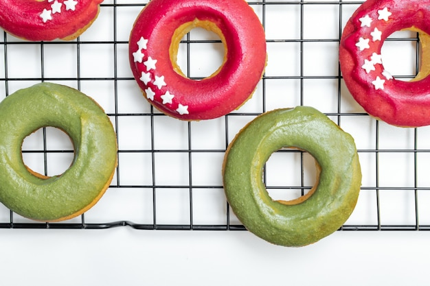 Odgórny widok świezi piec pączki z jaskrawym menchii i zieleni lodowaceniem, gwiazda kropi na chłodniczym stojaku