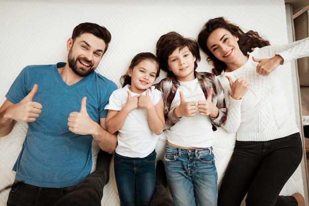 Odgórny widok szczęśliwa rodzina relaksuje na łóżku w sklepie