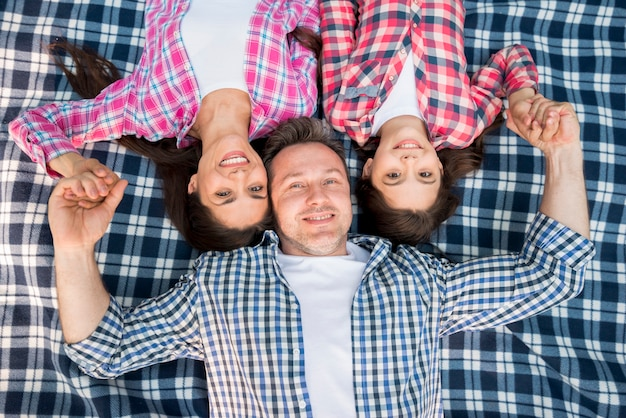 Odgórny widok szczęśliwy rodzinny lying on the beach na błękitnej koc