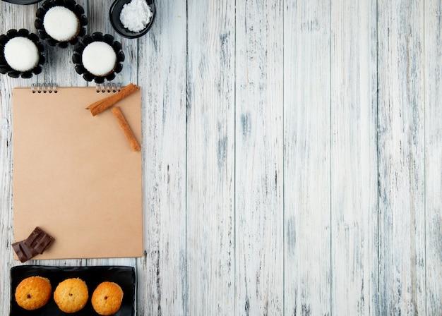 Odgórny widok szkicownik i asortowany wybór herbaciani ciastka na białym drewnianym tle z kopii przestrzenią