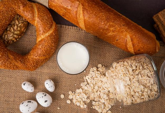 Odgórny widok szkło mleko i rozrzucony słój z płatkami owsianymi z chlebami na parciaku na czarnym tle