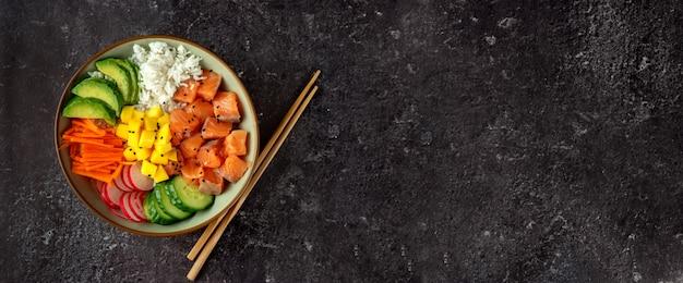 Odgórny widok szturchanie puchar z łososiem i avocado na zmroku stole, copyspace