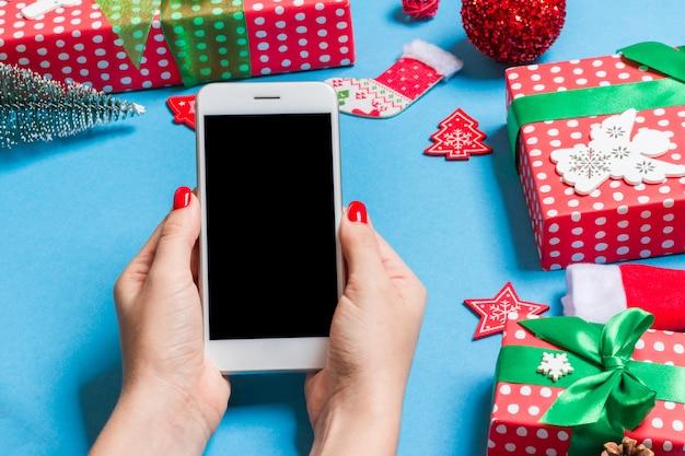 Odgórny widok telefon w żeńskiej ręce na świątecznym błękicie