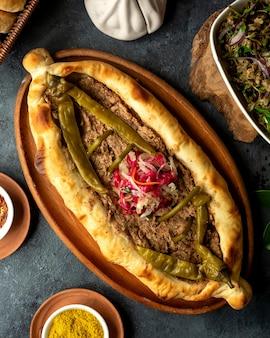Odgórny widok tradycyjna gruzińska kuchnia chaczapuri z mięsem i kiszonym gorącego chili zielonym pieprzem w drewnianym półmisku