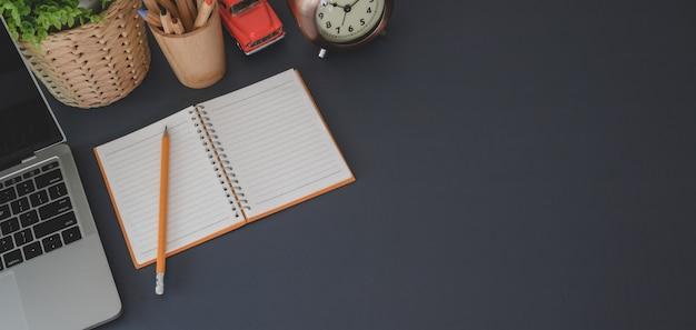 Odgórny widok trendu miejsce pracy z laptopem i biurowymi dostawami na czerń stole