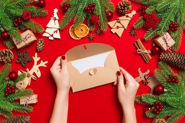 Odgórny widok trzyma kopertę na czerwieni kobieta robić wakacyjne dekoracje.