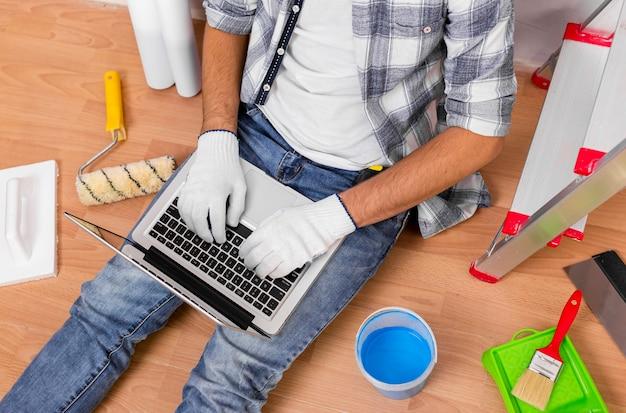 Odgórny widok trzyma laptop młody człowiek