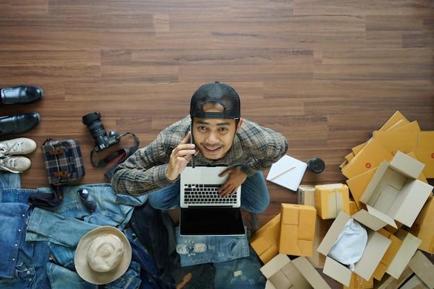 Odgórny widok trzyma mądrze telefonu pracującego laptop azjatykci mężczyzna