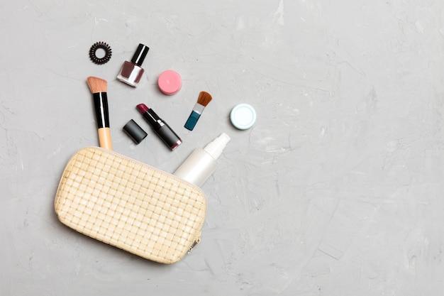 Odgórny widok uzupełniał produkty spadać z kosmetyk torby na cementowym tle.