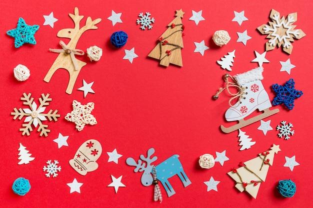 Odgórny widok wakacje zabawki i dekoracje na czerwonym bożenarodzeniowym tle.