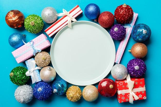 Odgórny widok wakacyjny położenie na kolorowych, talerzu, prezentach, baubles i bożenarodzeniowych dekoracjach, nowego roku obiadowy pojęcie