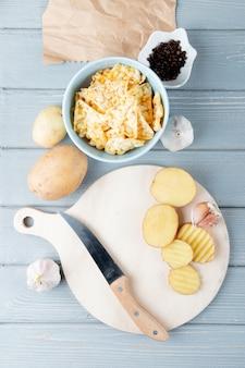 Odgórny widok warzywa jak pokrojony kartoflany czosnek z nożem na tnącej desce i chipsami z czarnym pieprzem na drewnianym tle