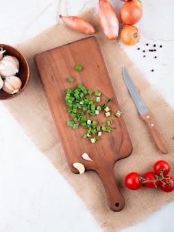 Odgórny widok warzywa jak rżniętą cebulę na tnącej deski czosnku pomidorze z nożem na białym tle z kopii przestrzenią