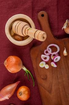 Odgórny widok warzywa jako cała i pokrojona cebula na tnącej deski czosnku w czosnek kruszarce na bordowym tle