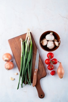 Odgórny widok warzywa jako cebulkowy czosnku pomidor z nożem na tnącej desce na białym tle z kopii przestrzenią