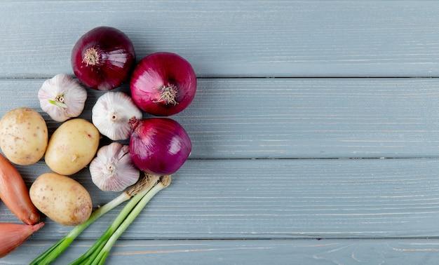 Odgórny widok warzywa jako kartoflany czosnku scallion, cebula na lewej stronie i drewniany tło z kopii przestrzenią